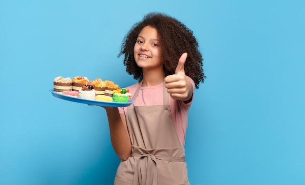 Mooie afro-tiener die zich trots, zorgeloos, zelfverzekerd en gelukkig voelt en positief glimlacht met de duimen omhoog. humoristisch bakkersconcept