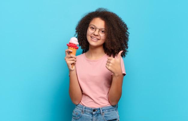 Mooie afro-tiener die zich trots, zorgeloos, zelfverzekerd en gelukkig voelt, positief glimlachend met duimen omhoog. zomer ijs concept