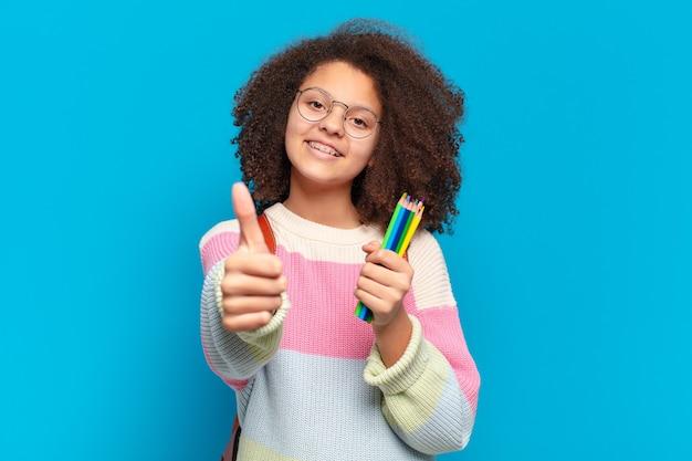 Mooie afro-tiener die zich trots, zorgeloos, zelfverzekerd en gelukkig voelt, positief glimlachend met duimen omhoog