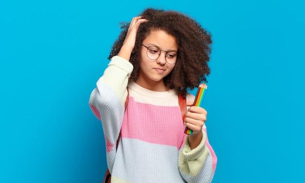 Mooie afro-tiener die zich verbaasd en verward voelt, hoofd krabt en opzij kijkt. studentenconcept