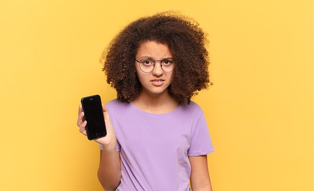 Mooie afro-tiener die zich verbaasd en verward voelt, met een domme, verbijsterde uitdrukking naar iets onverwachts kijkt en een cel vasthoudt