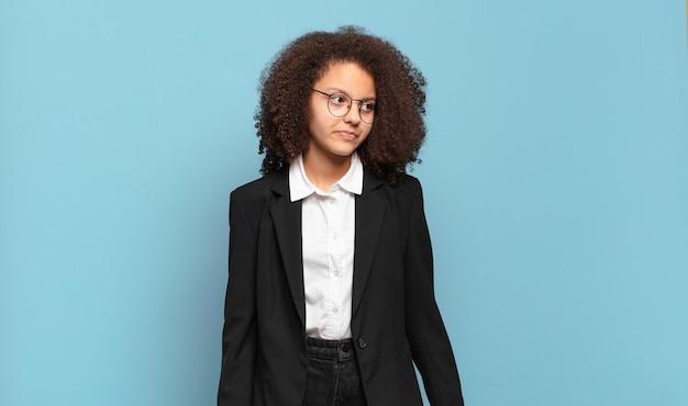Mooie afro-tiener die zich verdrietig, boos of boos voelt en opzij kijkt met een negatieve houding, fronsend van onenigheid. humoristisch bedrijfsconcept