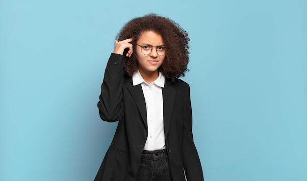 Mooie afro-tiener die zich verward en verbaasd voelt en laat zien dat je gek, gek of gek bent. humoristisch bedrijfsconcept