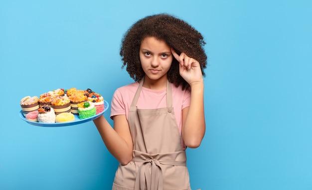 Mooie afro-tiener die zich verward en verbaasd voelt, laat zien dat je gek, gek of gek bent. humoristisch bakkersconcept