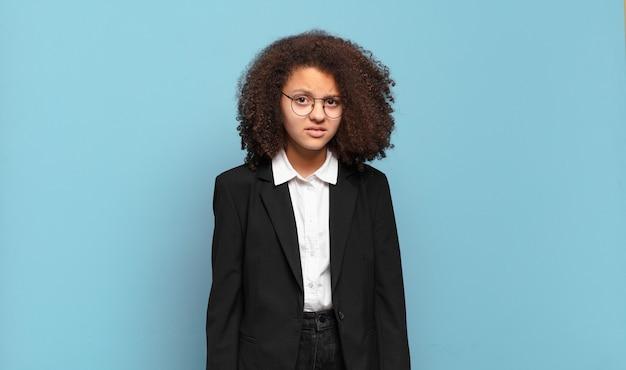 Mooie afro-tiener die zich verward en verward voelt, met een stomme, verbijsterde uitdrukking die naar iets onverwachts kijkt. humoristisch bedrijfsconcept