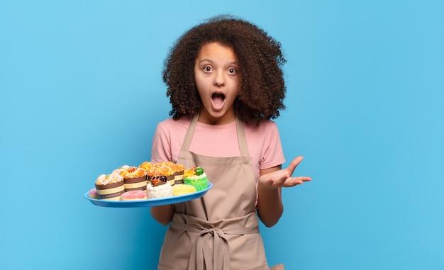 Mooie afro-tiener met open mond en verbaasd, geschokt en verbaasd over een ongelooflijke verrassing. humoristisch bakkersconcept