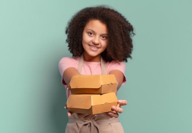 Mooie afro-tienermeisje-chef-kok met dozen voor hamburgers om mee te nemen