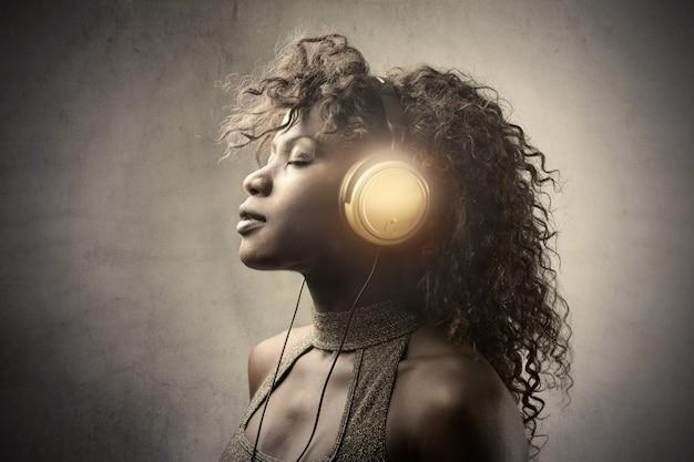 Mooie afro-vrouw die aan muziek luistert