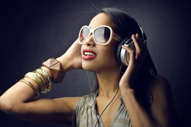 Mooie afro-vrouw die naar muziek luistert