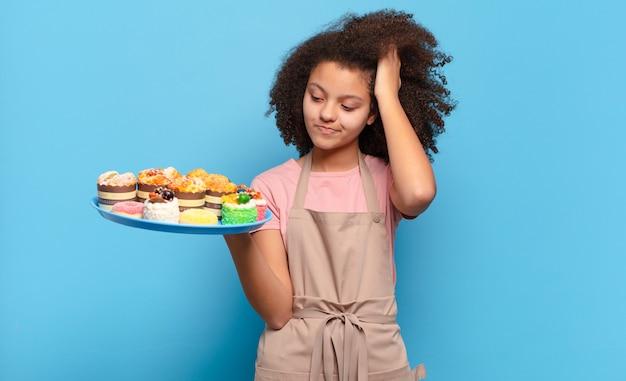 Mooie afro vrouw die zich verbaasd en verward voelt, haar hoofd krabt en naar de zijkant kijkt. humoristisch bakkersconcept