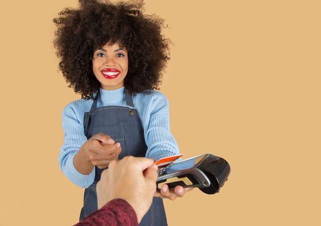 Mooie afro-vrouw in schort die een klant belast met een kaart