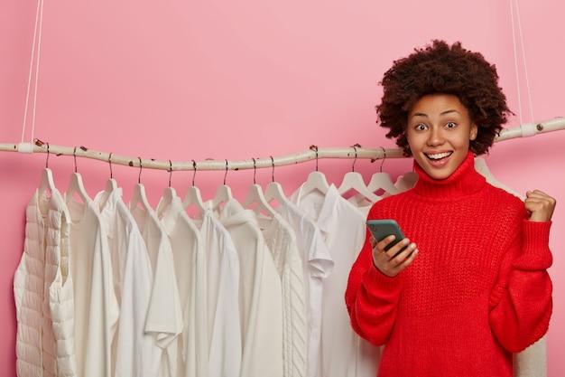 Mooie afro-vrouw met blije uitdrukking, succesvolle aankoop viert, staat tegen witte kleren op hangers kopie ruimte.