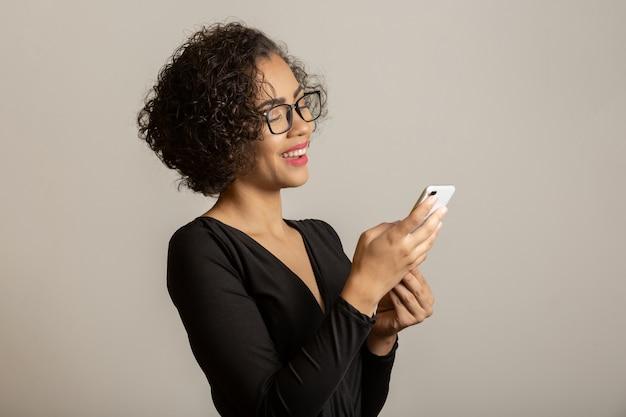 Mooie afrovrouw die, glazen draagt en smartphone gebruikt glimlacht