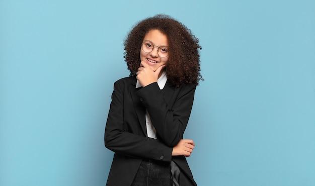 Mooie afrovrouw die met een gelukkige, zelfverzekerde uitdrukking glimlacht met hand op kin, zich afvraagt en naar de kant kijkt. humoristisch bedrijfsconcept