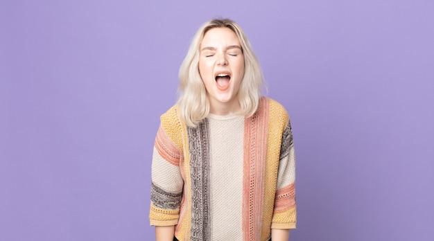 Mooie albino-vrouw die agressief schreeuwt, erg boos, gefrustreerd, verontwaardigd of geïrriteerd kijkt, nee schreeuwt