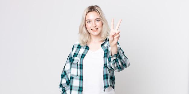 Mooie albino-vrouw die lacht en er gelukkig, zorgeloos en positief uitziet, gebarend overwinning of vrede met één hand
