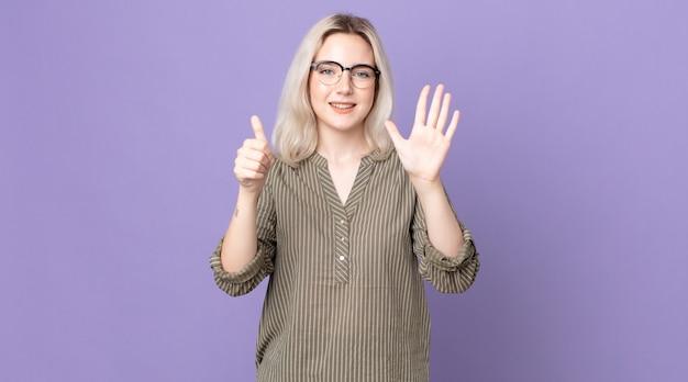 Mooie albino-vrouw die lacht en er vriendelijk uitziet, nummer zes of zesde toont met de hand naar voren, aftellend