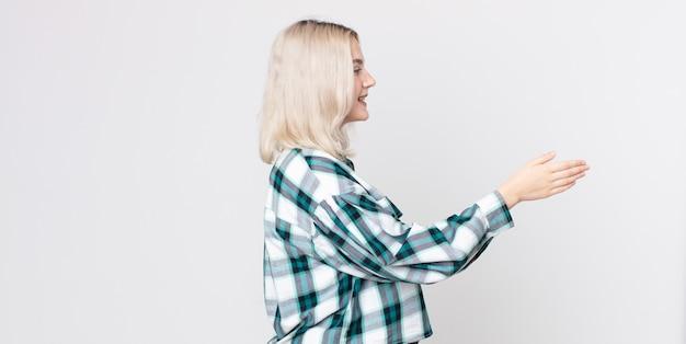 Mooie albino-vrouw die lacht, je begroet en een hand schudt om een succesvolle deal te sluiten, samenwerkingsconcept