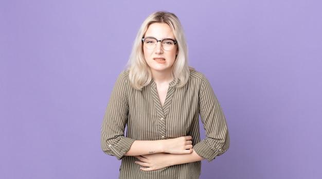 Mooie albino-vrouw die zich angstig, ziek, ziek en ongelukkig voelt, pijnlijke buikpijn of griep heeft