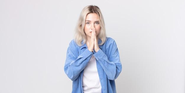 Mooie albino-vrouw die zich bezorgd, hoopvol en religieus voelt, trouw bidt met ingedrukte handpalmen, smekend om vergiffenis