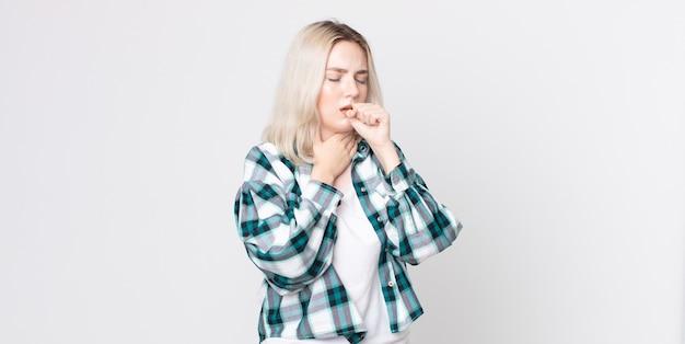 Mooie albinovrouw die zich ziek voelt met een zere keel en griepsymptomen, hoest met bedekte mond