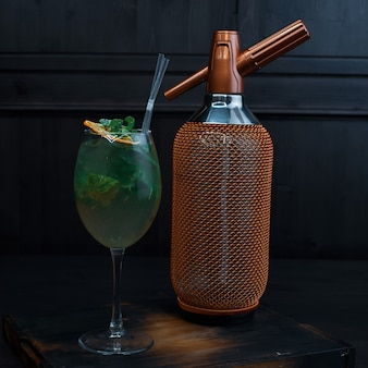 Mooie alcoholische cocktail in een elegant glas met toevoeging van tequila en verse muntblaadjes staat op een vintage tafel in een restaurant in de buurt van de gouden luxe fles. exotische drank