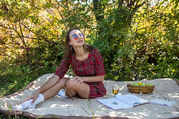 Mooie alleenstaande vrouw in rode jurk zittend op picknickdeken in park, lifestyle