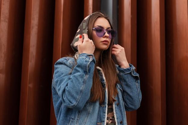 Mooie amerikaanse jonge hipster vrouw in stijlvol blauw spijkerjasje in paarse trendy bril poseren in de buurt van moderne metalen gestreepte muur in de stad. mooi meisje model in modieuze jeugdkleding buitenshuis.