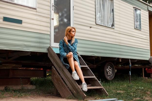 Mooie amerikaanse vrouw in stijlvolle jeanswear met schoenen zitten in de buurt van een metalen vintage aanhangwagen