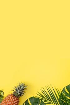 Mooie ananas op tropische palm monstera bladeren geïsoleerd op heldere pastel gele achtergrond, bovenaanzicht, plat lag, overhead boven zomerfruit.