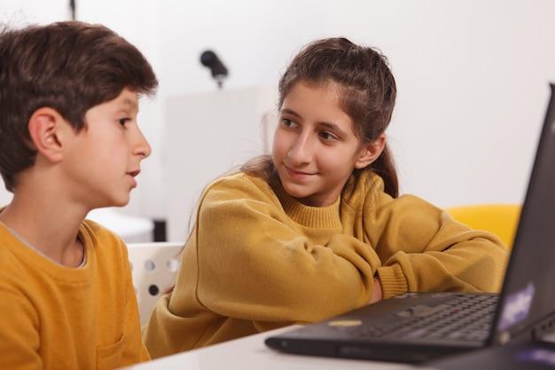 Mooie arabische tiener meisje praten met haar kleine broertje terwijl huiswerk samen op een laptop