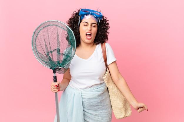 Mooie arabische vrouw die agressief schreeuwt en erg boos kijkt met een bril. vissers concept