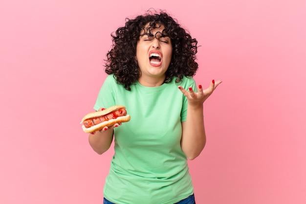 Mooie arabische vrouw die boos, geïrriteerd en gefrustreerd kijkt en een hotdog vasthoudt