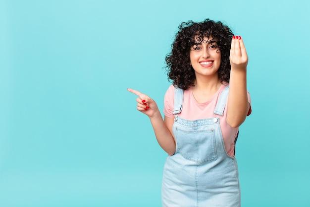 Mooie arabische vrouw die capice of geldgebaar maakt en zegt dat je moet betalen