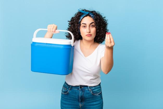 Mooie arabische vrouw die capice of geldgebaar maakt, zegt dat je moet betalen en een draagbare koelkast vasthoudt