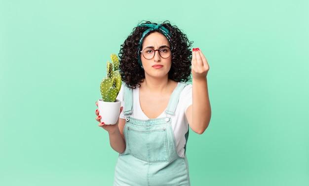 Mooie arabische vrouw die capice of geldgebaar maakt, zegt dat je moet betalen en een potcactus vasthoudt