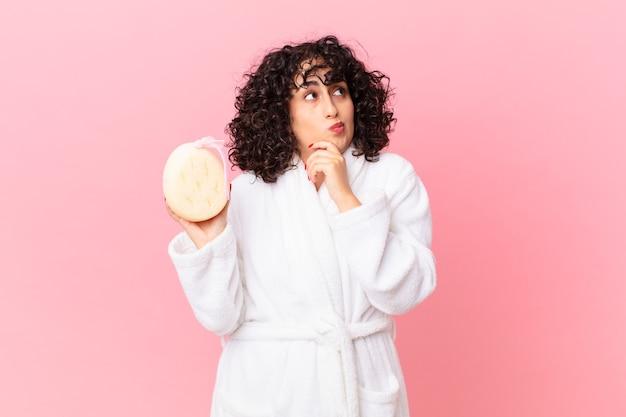 Mooie arabische vrouw die denkt, zich twijfelachtig en verward voelt terwijl ze een badjas draagt en een spons vasthoudt