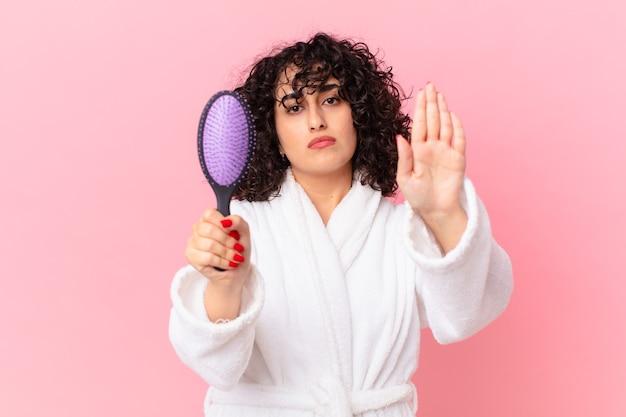 Mooie arabische vrouw die een badjas draagt en een haarborstel vasthoudt