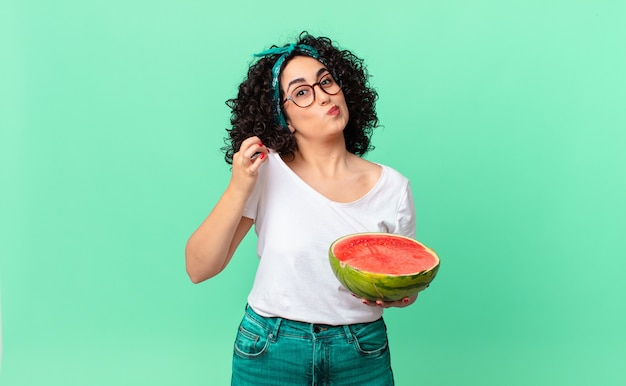 Mooie arabische vrouw die er arrogant, succesvol, positief en trots uitziet en een watermeloen vasthoudt. zomer concept
