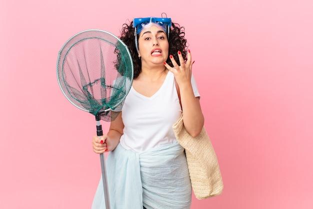 Mooie arabische vrouw die er wanhopig, gefrustreerd en gestrest uitziet met een veiligheidsbril. vissers concept