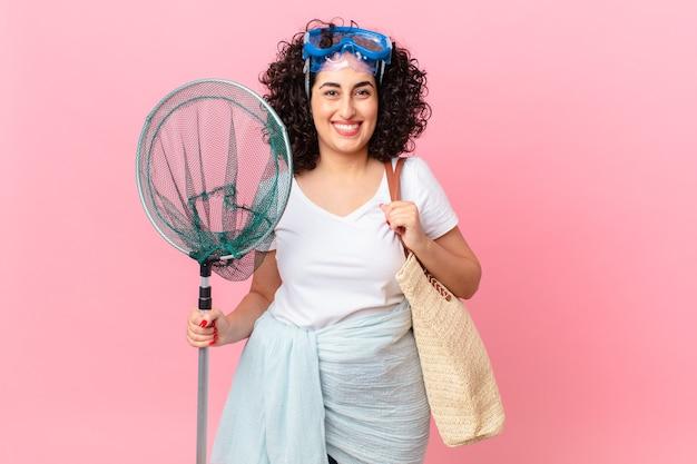 Mooie arabische vrouw die gelukkig lacht met een hand op de heup en zelfverzekerd met een bril. vissers concept