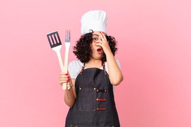 Mooie arabische vrouw die geschokt, bang of doodsbang kijkt en haar gezicht bedekt met de hand. barbecue chef-kok concept