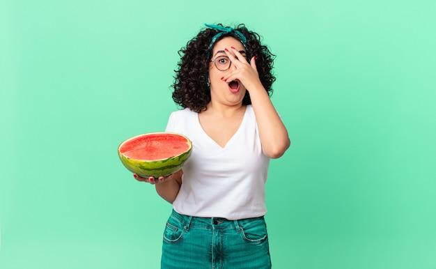 Mooie arabische vrouw die geschokt, bang of doodsbang kijkt, haar gezicht bedekt met de hand en een watermeloen vasthoudt. zomer concept