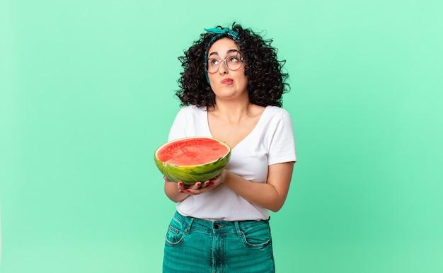 Mooie arabische vrouw die haar schouders ophaalt, zich verward en onzeker voelt en een watermeloen vasthoudt. zomer concept
