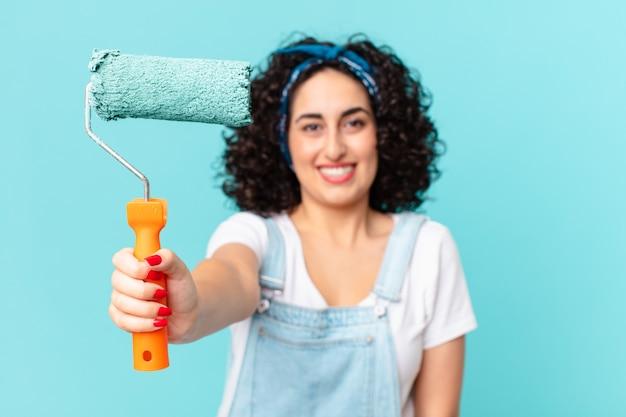 Mooie arabische vrouw die het concept van de huismuur schildert