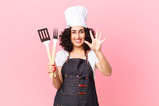 Mooie arabische vrouw die lacht en er vriendelijk uitziet, met nummer vijf. barbecue chef-kok concept