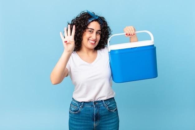 Mooie arabische vrouw die lacht en er vriendelijk uitziet, nummer vier toont en een draagbare koelkast vasthoudt