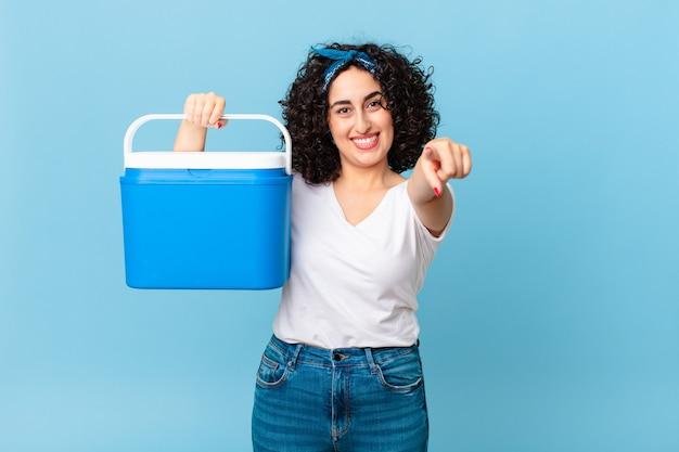 Mooie arabische vrouw die naar de camera wijst en jou kiest en een draagbare koelkast vasthoudt