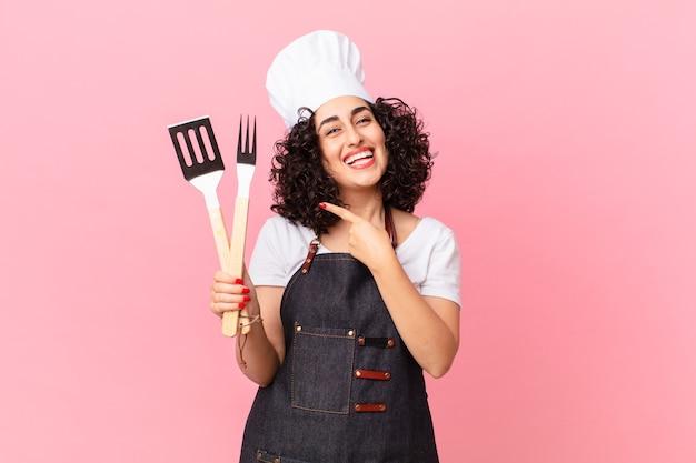 Mooie arabische vrouw die opgewonden en verrast kijkt en naar de zijkant wijst. barbecue chef-kok concept