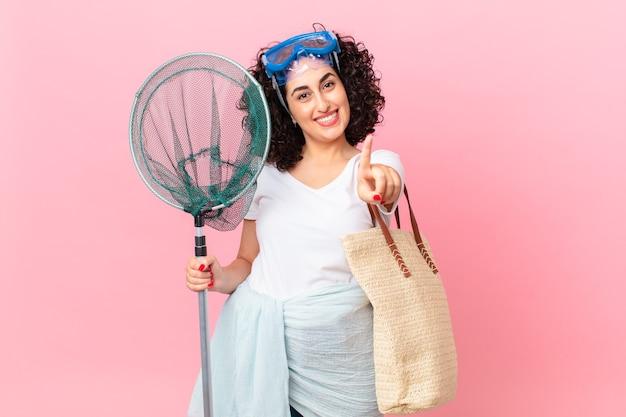 Mooie arabische vrouw die trots en zelfverzekerd glimlacht en nummer één maakt met een bril. vissers concept
